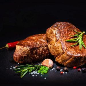 grilled beef fillet steaks with herbs and spices on dark background